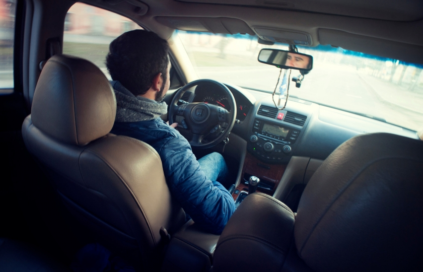 Man wearing blue jacket sitting inside a car while driving